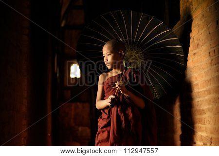 Young novice monks walking thru a Buddhist temple, Bagan, Myanmar.