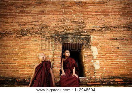 Young Buddhist novice monks at outside monastery, pagan, Myanmar.