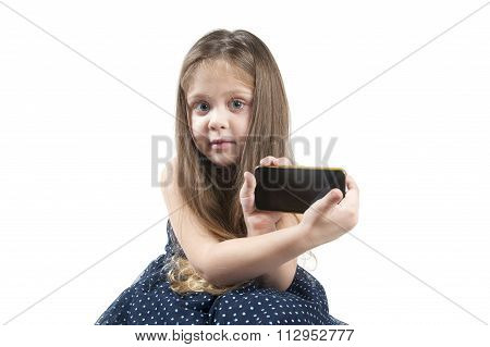 Portrait Of A Little Girl With Mobile Phone In Hand..