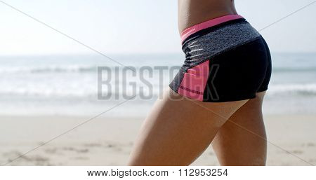 Bottom of a lady in fitness wear against beach background