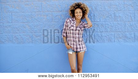 Young woman in summer clothes against blue stone wall flirting with camera