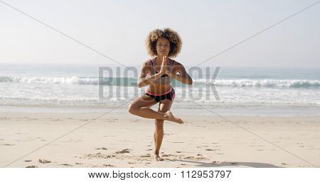 Woman is doing yoga standing on one leg on the beach