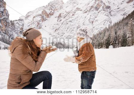 Mother Blowing Snow On Child Among Snow-capped Mountains