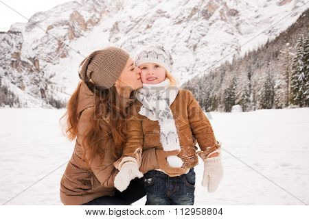 Mother Kissing Child Outdoors Among Snow-capped Mountains