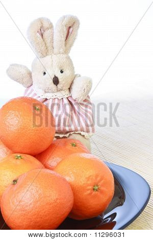 Toy little doe rabbit and pile of ripe fresh tangerines on plate