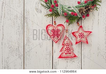 Christmas toys (christmas tree, heart, star) hanging over wooden background