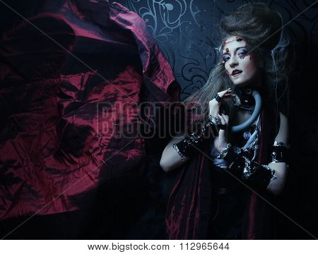 Young woman with creative make up in a red raincoat. Halloween theme. Zombie theme.