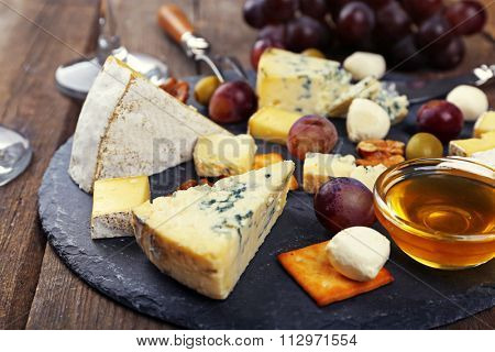 Cheese for tasting on wooden table, closeup