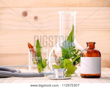 Alternative Health Care Fresh Herbal In Laboratory Glassware  With  Stethoscope On Wooden Background
