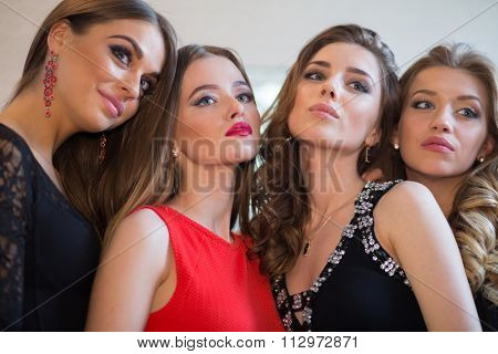 Closeup portrait of four beautiful women, focus on girl in red dress.