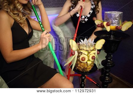 Two young women resting with the hookah, focus on the hookah.