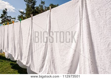 Fresh Clean White Towels Drying On Washing Line In Outdoor