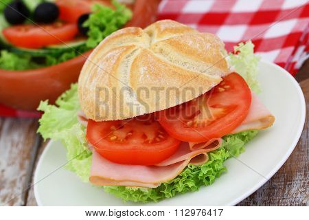 Bread roll with smoked ham, lettuce and tomatoes