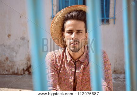 Handsome Man With Hat Behind The Bars