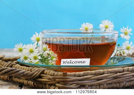 Welcome card with cup of chamomile tea with fresh chamomile flowers on wicker tray