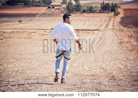 Fashion Man Walk Alone On The Field