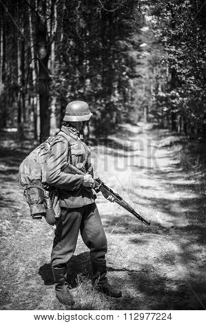Unidentified re-enactor dressed as German soldier with rifle sta
