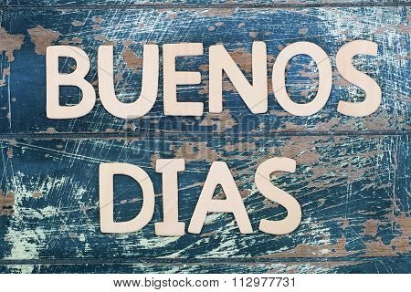 Buenos dias (good morning in Spanish) written on rustic wooden surface