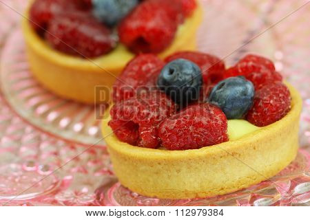 Crunchy and creamy tartelette with raspberries and blueberries, closeup