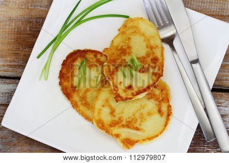 Potato fritters garnished with spring onions on white plate on rustic wooden surface