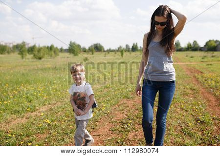Young Beautiful Mother With Her Son Walking