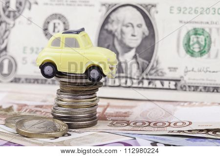 toy car and money: dollars, rubles closeup