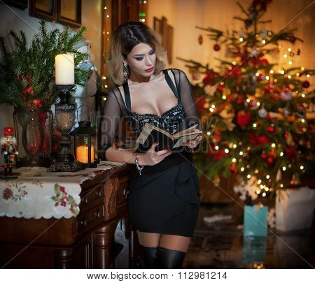 Beautiful sexy woman in elegant black dress with Xmas tree in background