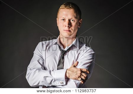 Portrait of serious elegant handsome young man in classic suit toasting with ring. Undo shirt.