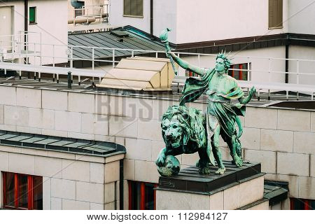 Statue on roof of entrance to the bank Czech National Bank in Prague, Czech Republic.