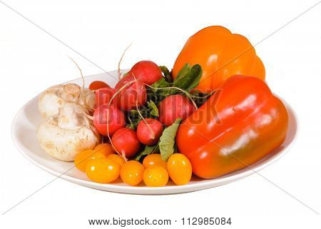 Fresh vegetables - peppers, radishes, mushrooms, tomato's, on a white plate over a white background