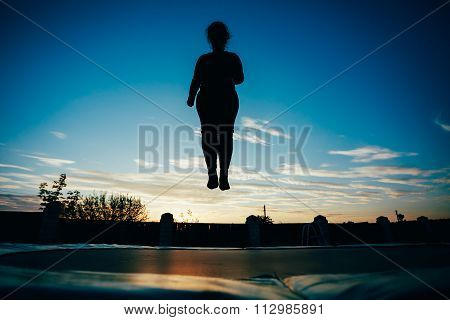 Silhouette Of Beautiful Plus Size Young Woman Girl Jumping On Tr