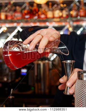 Bartender is pouring juice to a measuring glass