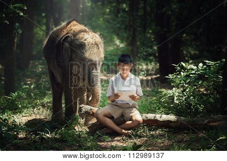 Boy Reading Book With Elephant At Elephant Village School In Thailand.