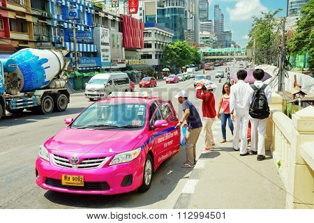 BANGKOK, THAILAND - APRIL 29, 2015: Pedestrians stopped a taxi in Bangkok. There are 150,000 taxis in Bangkok. All are metered with the starting fee of 35 Baht for the first 3 kilometers.