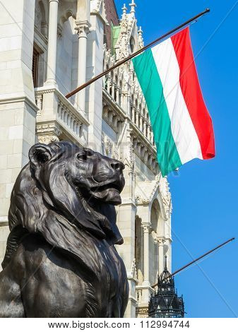 Flag Of Hungary And The Stone Lion Protecting An Entrance To The Hungarian Parliament
