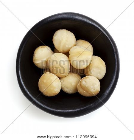 Macadamia nuts in black bowl.  Overhead view.  Isolated on white.