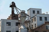 stock photo of yesteryear  - Large abandoned old grain mill of yesteryear - JPG