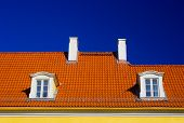 pic of gabled dormer window  - orange roof with two windows and chimneys against blue sky - JPG