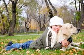 stock photo of laika  - Boy playing in autumn park with a golden retriever - JPG