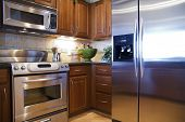 stock photo of kitchen appliance  - a beautiful bright modern kitchen with stainless steel appliances - JPG