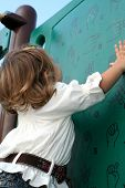foto of fingerspelling  - little girl studying a wall showing sign language at a playground - JPG