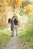 image of native american ethnicity  - Young couple dancing in colorful autumn forest