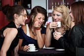 stock photo of foursome  - A foursome of pretty girls laughing in a cafe - JPG