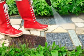 picture of pressure-wash  - Person in red gumboots cleaning garden alley with a pressure washer - JPG