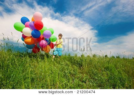 Happy boy enjoy on meadow with balloons