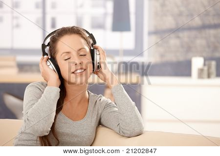 Young woman listening to music at home, sitting on sofa, smiling, using headphones, eyes closed.?