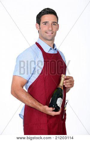 Waiter offering bottle of champagne