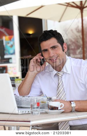 Businessman drinking an expresso in a cafe while talking on a cellphone