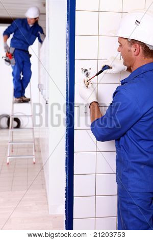 an electrician screwing an electrical outlet and a colleague on a stepladder