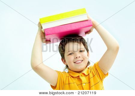 Portrait of smiling lad with stack of books looking at camera